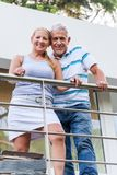 Senior couple standing on terrace modern house. Senior couple embrace standing on terrace balcony of modern house Stock Photo