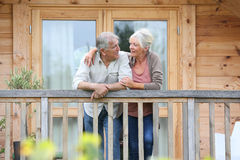 Senior couple standing on terrace. Senior couple standing oustide log cabin in countryside Stock Photo
