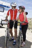 Senior Couple Standing By Their Bicycles And Looking At Each Other. Full length of a senior couple standing by their bicycles and looking at each other Stock Images