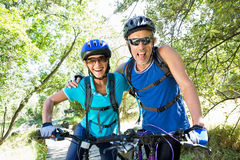 Senior couple standing with their bikes. In a forest Stock Images