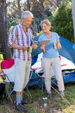 Senior couple standing beside their tent Stock Images