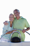 Senior couple standing together on boat, cut out stock image