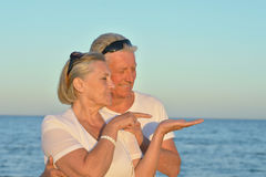 Senior couple standing together. Happy senior couple standing together on seashore, women pointing somewhere Stock Photography