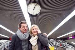 Senior couple standing at the underground platform, calling Stock Images