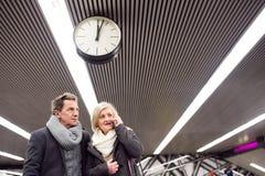 Senior couple standing at the underground platform, calling Stock Photography