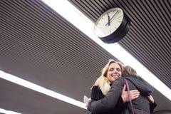 Senior couple standing at the underground platform, hugging Stock Photo