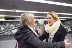 Senior couple standing at the underground platform, hugging Stock Images