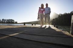 Senior Couple Standing On Wooden Jetty Looking Out Over Lake Stock Images