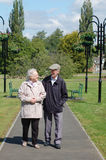 Senior couple strolling in the park. A senior couple walking in a park on a sunny day Royalty Free Stock Photo