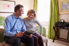 Senior couple study a guide brochure together in hotel room Stock Photography