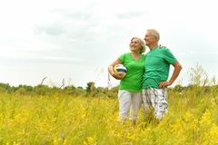 Senior couple in summer field with ball Royalty Free Stock Photography