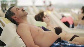 Senior couple sunning at the beach stock video
