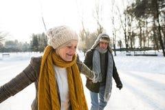 Senior couple in sunny winter nature ice skating. Beautiful senior women and men in sunny winter nature ice skating Stock Image