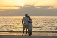 Senior Couple Sunset Tropical Beach. Senior men and women couple embracing at sunset or sunrise on a deserted tropical beach Royalty Free Stock Image