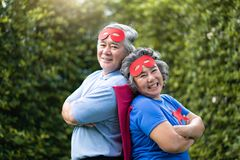 Senior couple in Superhero costume lauging with arms crossed royalty free stock photography