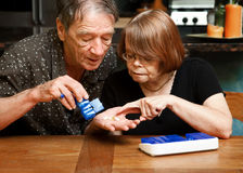 Senior couple with daily supplements Royalty Free Stock Images