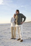 Senior couple in sweaters together on beach. Affectionate senior couple in warm clothing standing together on beach Royalty Free Stock Images