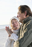 Senior couple in sweaters together on beach. Affectionate senior couple in warm clothing standing together on beach Royalty Free Stock Photos