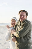 Senior couple in sweaters together on beach. Affectionate senior couple in warm clothing standing together on beach Stock Images