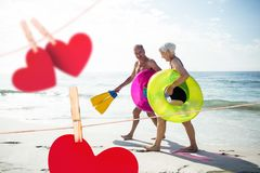 Senior couple with swim ring and swimfin walking on beach. Composite image of red heart and senior couple holding swim ring and swimfin walking on beach Stock Photo