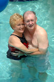 Senior couple in swimming pool stock photography