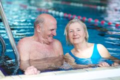 Senior couple swimming in pool. Happy healthy active senior couple having fun together in the swimming pool Royalty Free Stock Image