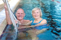 Senior couple swimming in pool stock photos