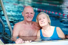 Senior couple swimming in pool. Happy healthy active senior couple having fun together in the swimming pool Stock Image