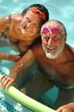 Senior couple swimming together. Happy retired couple having fun in the swimming pool in bright matching goggles Stock Image