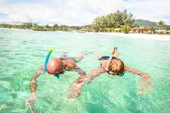 Senior couple swimming on tropical paradise beach in Koh Lipe. Senior couple vacationer swimming together on tropical Koh Lipe sea in Thailand - Snorkeling tour Stock Image