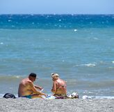 Senior couple in swimwear, playing cards on the beach.