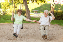 Senior couple swinging in the park. Senior couple having fun on park swings Royalty Free Stock Photo