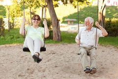 Senior couple swinging in the park. Senior couple having fun on park swings Stock Photography