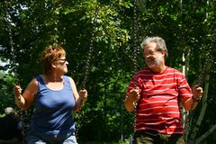 Senior couple on swings Royalty Free Stock Photo