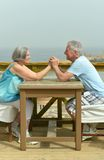 Senior couple at table at beach Royalty Free Stock Images
