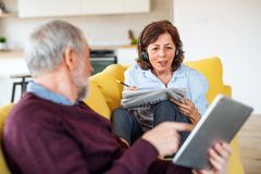 Senior couple with tablet and headphones sitting on sofa indoors at home. Senior couple with tablet and headphones sitting on sofa indoors at home, relaxing royalty free stock photo
