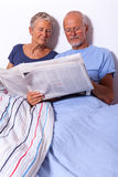Senior Couple with Tablet and Newspaper in Bed Royalty Free Stock Images
