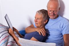Senior Couple with Tablet and Newspaper in Bed Stock Image