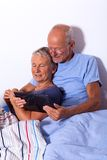 Senior Couple with Tablet and Newspaper in Bed Stock Images
