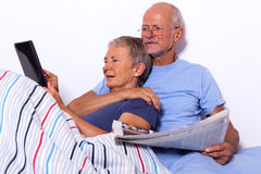 Senior Couple with Tablet and Newspaper in Bed Royalty Free Stock Image