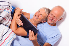 Senior Couple with Tablet and Newspaper in Bed Stock Photos