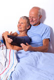Senior Couple with Tablet and Newspaper in Bed Royalty Free Stock Photos