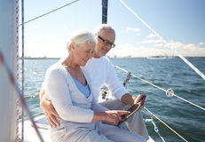 Senior couple with tablet pc on sail boat or yacht. Sailing, technology, tourism, travel and people concept - happy senior couple with tablet pc computer on sail stock images