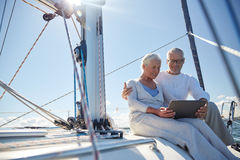 Senior couple with tablet pc on sail boat or yacht Royalty Free Stock Photos