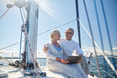 Senior couple with tablet pc on sail boat or yacht Stock Image