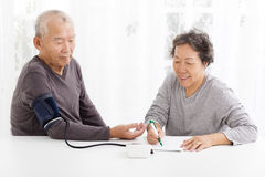 Senior couple taking  blood pressure in living room Royalty Free Stock Image