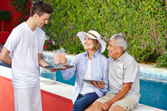 Senior couple taking cocktails at pool Stock Image