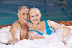 Senior couple taking foam bubble bath Royalty Free Stock Photography