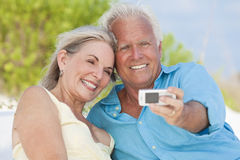 Senior Couple Taking Photographs On Cell Phone. Happy senior man and woman couple laughing and taking photographs with a cell phone on a tropical beach royalty free stock image