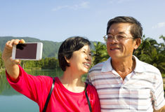 Senior couple taking picture by themselves in outdoor Stock Image